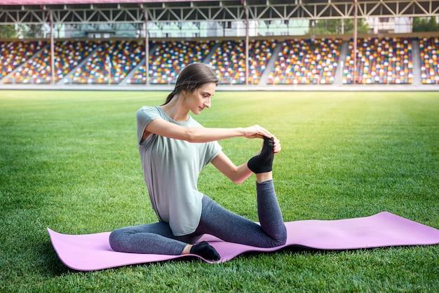 Donna seduta sulla stuoia su erba verde e facendo esercizi di yoga
