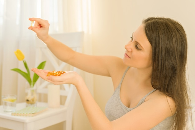 La donna seduta mattina a letto prende vitamine, olio di pesce omega-3 vitamina e