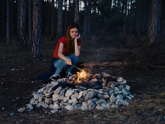 Donna seduta vicino al falò la sera delle vacanze nella foresta travel