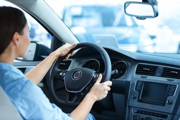 Donna che si siede in una nuova automobile al salone dell'automobile che tiene un volante