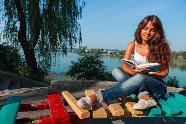 Donna seduta su una panchina del parco e leggere un libro. donna che legge all'aperto