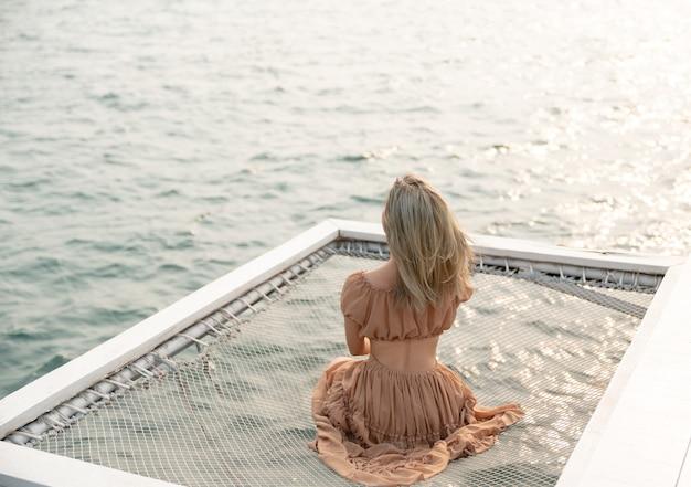 Donna seduta su un molo con sfondo mare, sedersi in rete in riva al mare.