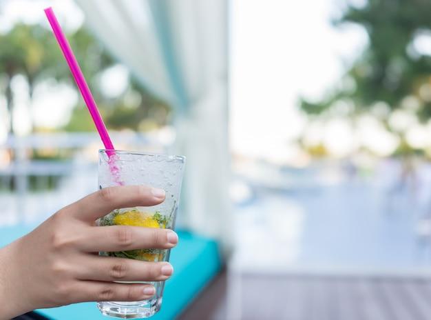 Donna seduta sulla piscina del resort e bere succo