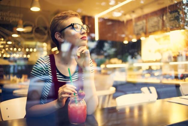 Donna seduta in un ristorante con un cocktail di solitudine sguardo pensieroso
