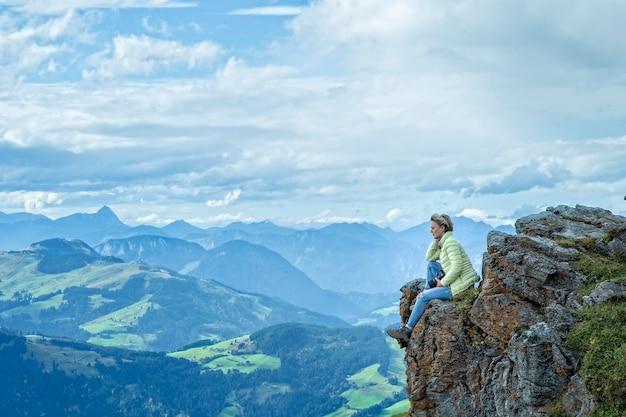 Una donna seduta su una roccia alpi austriaveduta panoramica dall'alto