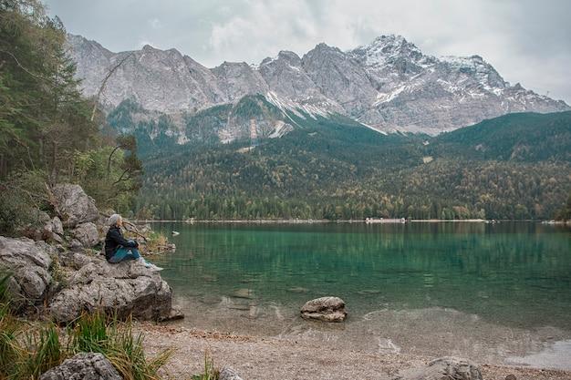 Una donna seduta sulle rocce vicino al lago. alpi germania.