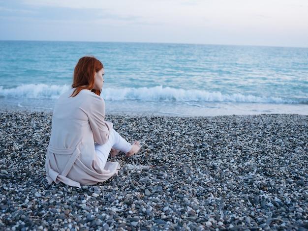 Donna seduta in riva al mare e nuvole cielo blu vista posteriore.