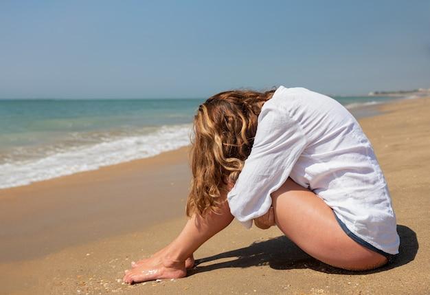 Donna seduta sulla riva che copre il viso con le gambe
