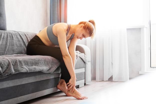 La donna seduta sul divano tiene il suo infortunio al piede, sensazione di dolore. assistenza sanitaria e concetto medico.