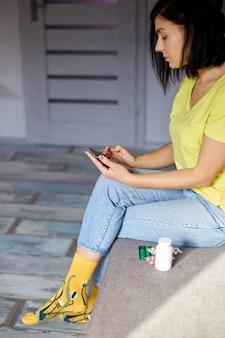Donna seduta sul divano con blister di pillole utilizzando la farmacia online, acquistando la farmacia su internet