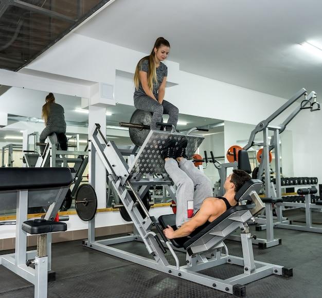 Donna seduta su attrezzatura sportiva come peso per uomo