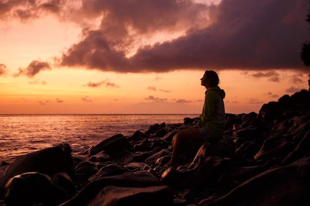 Donna seduta su una pietra e guardando il mare al tramonto