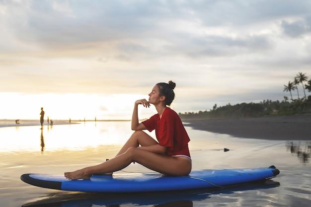 Donna che si siede sulla tavola da surf sulla spiaggia dopo la sua sessione di surf