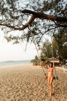 Donna seduta sull'altalena sulla spiaggia tropicale, isola paradisiaca.