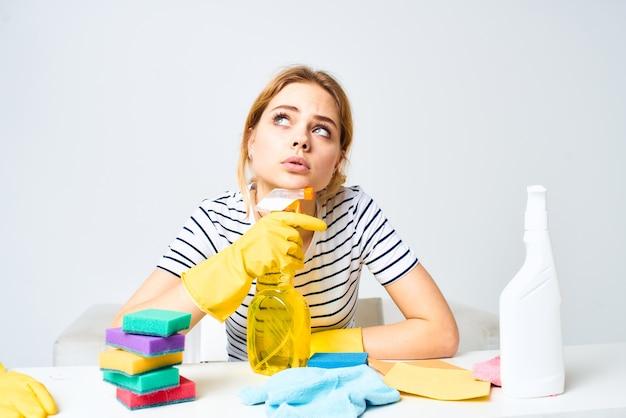 Donna seduta al tavolo detersivo stracci spugne cura della casa luce interna.