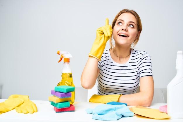 Donna seduta al tavolo guanti di gomma pulizia servizio detergente lavori domestici.