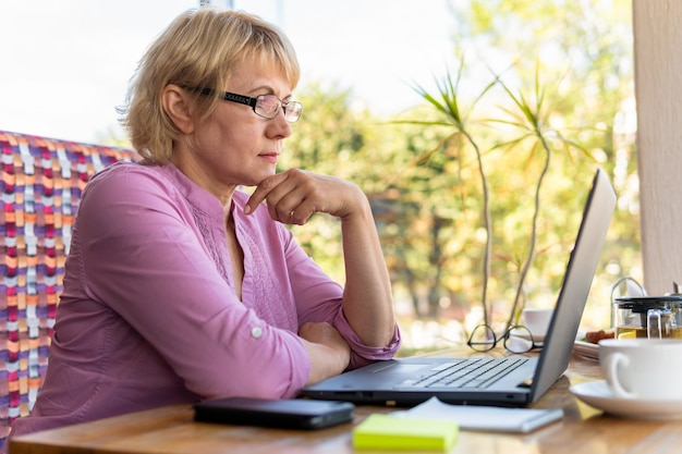 Una donna seduta a un tavolo con una tazza di tè e un laptop che lavora in un bar