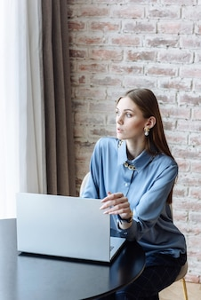 Donna seduta a tavola con il computer portatile