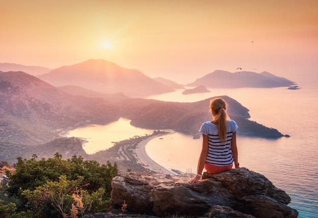 Donna seduta sulla cima di roccia e guardando la spiaggia e le montagne al tramonto