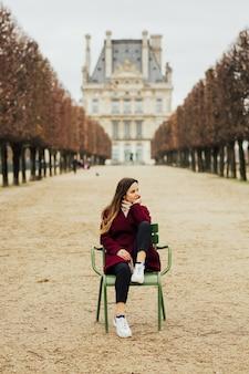 Donna seduta sulla tradizionale sedia verde nel giardino delle tuileries a parigi, francia.