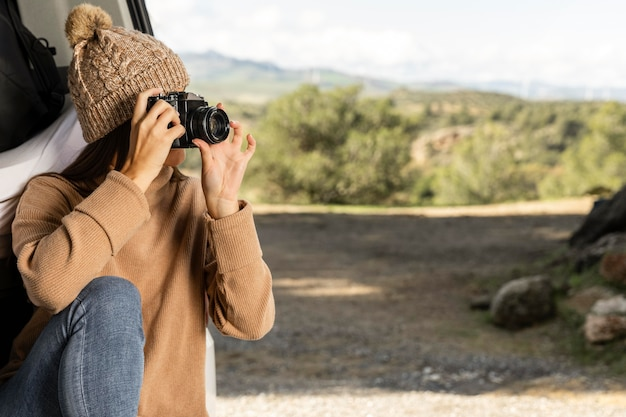 Donna seduta nel bagagliaio dell'auto durante un viaggio e tenendo la fotocamera