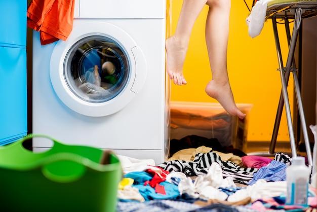 Donna seduta sulla lavatrice in lavanderia. vista ravvicinata della macchina e delle gambe