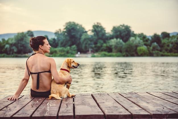 Donna che si siede con il cane sul bacino