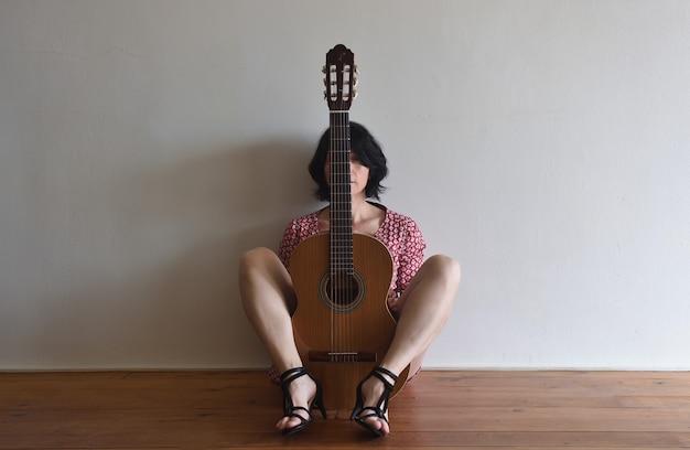 Una donna seduta con una chitarra