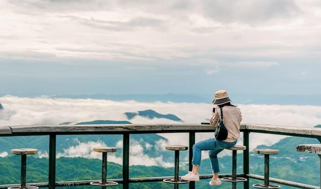 Donna seduta sul balcone di legno guardando la montagna e la nebbia in viaggio