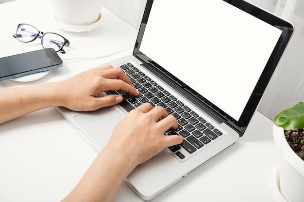 Donna seduta al tavolo dell'area di lavoro sta lavorando al computer portatile schermo vuoto digitando la tastiera