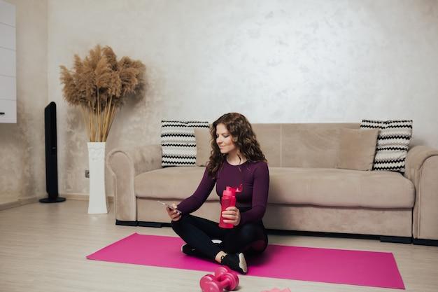Donna seduta su un tappetino da yoga usando il telefono e bevendo acqua dopo l'allenamento