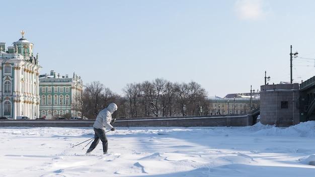Sciatore della donna che guida sul ghiaccio congelato del lago
