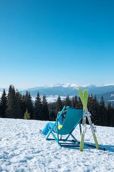 Sciatore della donna che si siede sulla sedia con la stazione sciistica di vista panoramica delle belle montagne. vacanze invernali