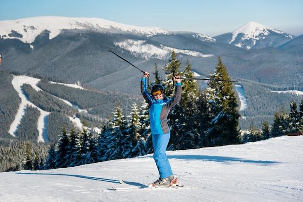 Sciatore della donna sul pendio alla stazione sciistica in inverno