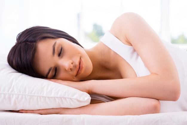 Donna che dorme. bella giovane donna sorridente che dorme nel letto