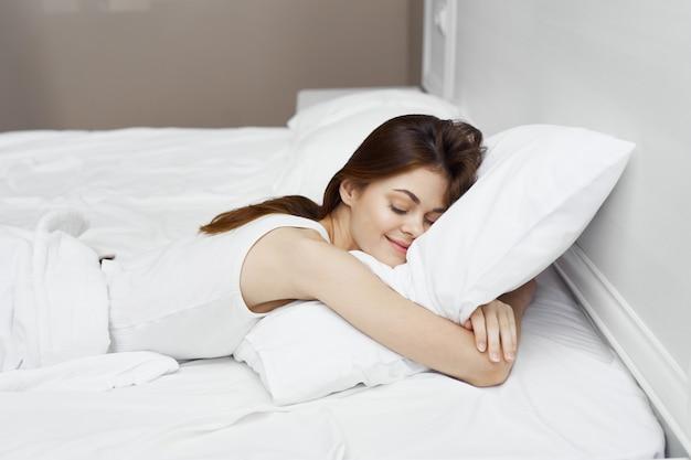 Donna che dorme sul letto conforta il cuscino di riposo mattina