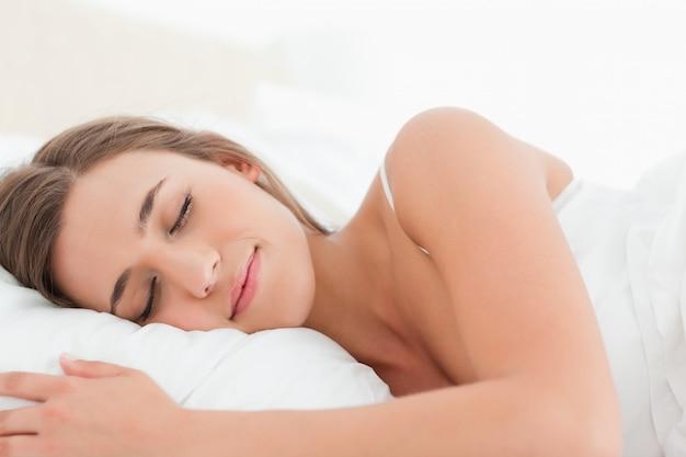 Donna che dorme nel letto, la testa sul cuscino