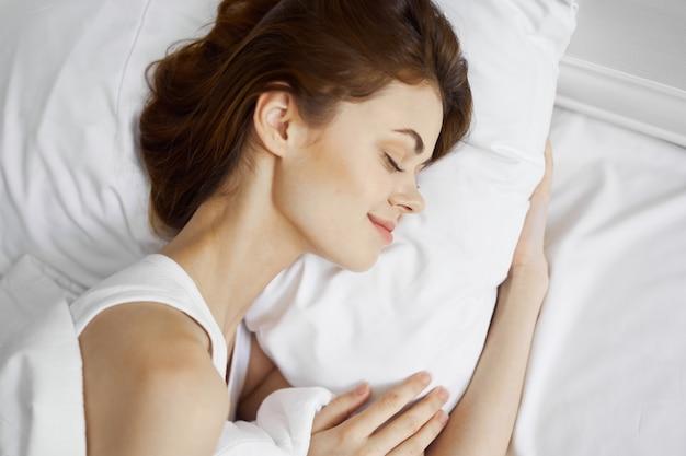 Donna che dorme sul letto morbido cuscino comfort mattina riposo
