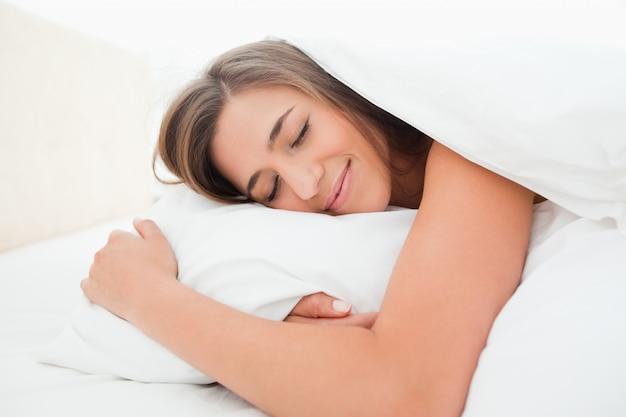 Donna che dorme nel letto, con un sorriso e la testa sul cuscino