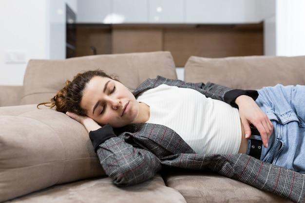 La donna dorme a casa sul divano, a riposo dopo il lavoro