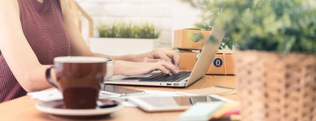 Il piccolo imprenditore della donna, impresa avvia il lavoro concettuale e giovane dell'imprenditore con il negozio online del prodotto di vendita del computer portatile, ampia dimensione dell'insegna