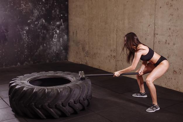 Donna che fracassa la grande gomma con la mazza durante l'allenamento intenso in palestra in forma