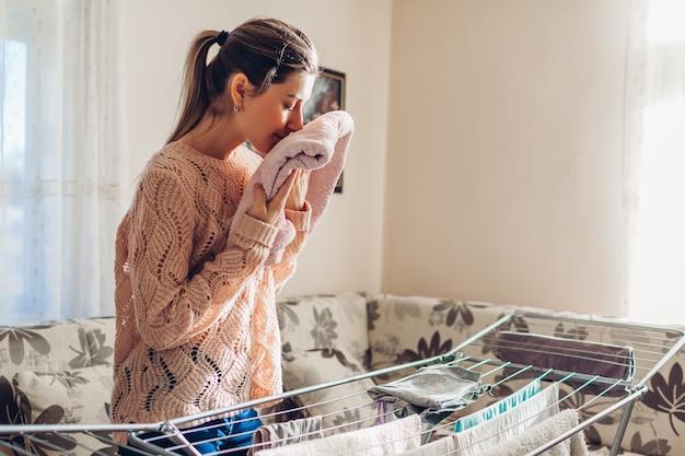 L'odore della donna ha raccolto i vestiti puliti dall'essiccatore in mucchio. pulizie domestiche e faccende domestiche