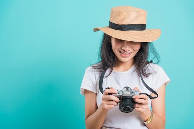 Sorriso della donna in cappello di estate che sta con la macchina fotografica mirrorless della foto