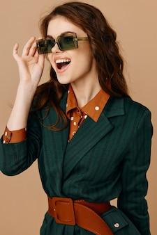 Fondo isolato moda della giacca degli occhiali da sole di sorriso della donna