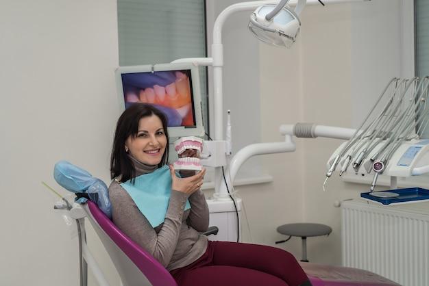 Donna sorridente in odontoiatria con modello della mascella