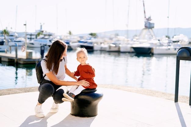 Donna che sorride alla sua bambina mentre fa una passeggiata in un porto turistico.