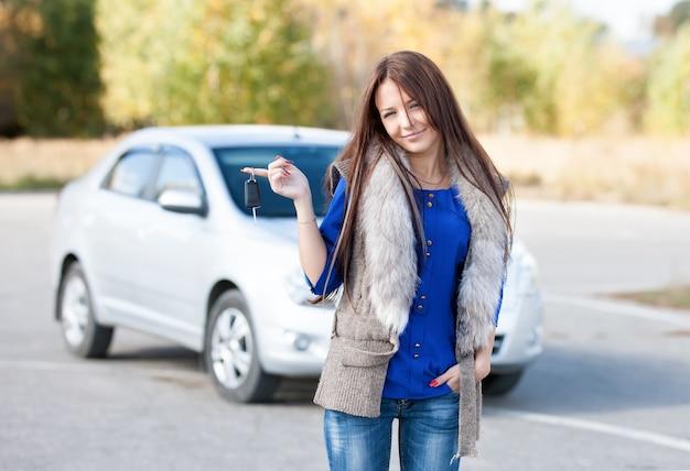 Donna sorridente che mostra le chiavi della macchina nuove
