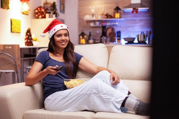 Donna che sorride mentre guarda un film comico di natale in televisione che riposa sul divano