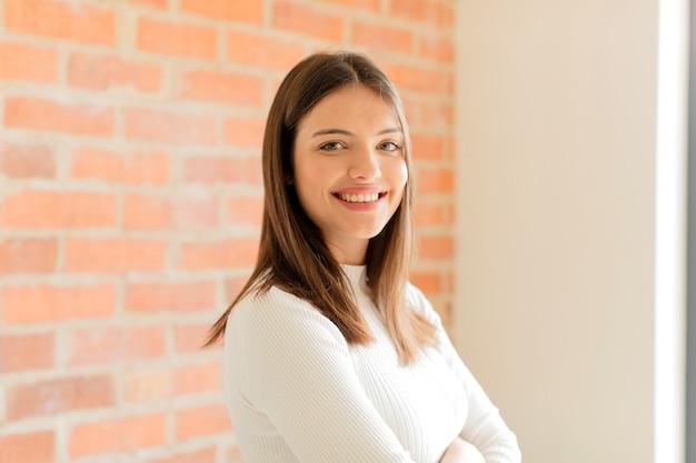 Donna sorridente con le braccia incrociate e un'espressione felice, fiduciosa, soddisfatta, vista laterale